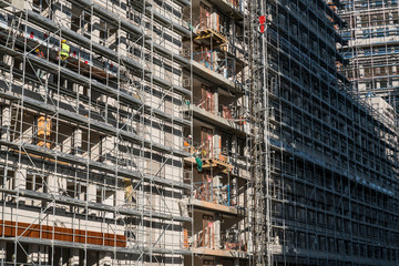 Construction worker works on building facade in construction site