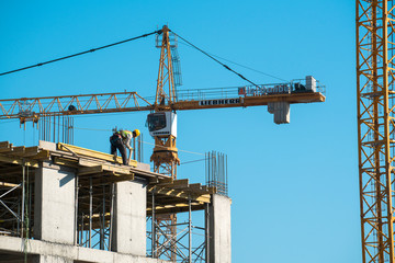 Construction worker works top of the building with crane background