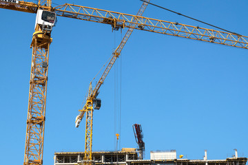 Crane on construction site with blue sky background