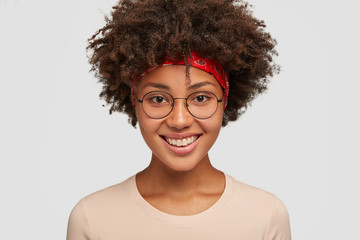 Close up shot of friendly looking cheerful African Amrican female with tender expression, pleasant smile, rejoices amazing trip on summer vacation, wears round glasses, models in white studio
