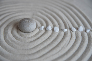 Photo sur Plexiglas Zen pierres a sable Gray zen stones on the sand with wave drawings. Concept of harmony, balance and meditation, spa, massage, relax