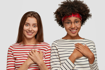 Two delighted happy multiethnic women hold hands on breast, smile joyfully and remember great moment, appreciate somebodys support, feel thankful, wears striped jumpers, isolated over white background