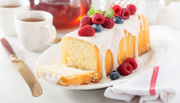 Butter vanilla cake for breakfast with glaze and fresh berries.