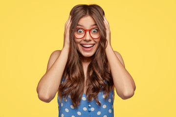 Excited happy lady listens awesome story, touches head with both hands, feels entertained, wears red rim spectacles and polka dot dress, stands against yellow background, expresses positive reaction