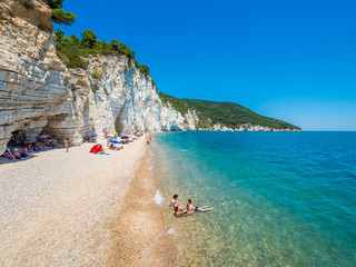 APULIA, IT - Jul 19, 2018: Mattinata Faraglioni stacks and beach coast of Baia Delle Zagare, Vieste Gargano, Apulia, Italy