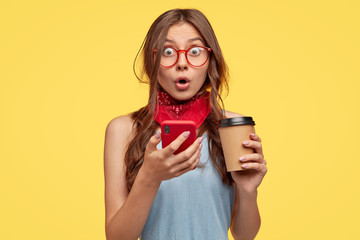 Emotive surprised teenager girl opens mouth, feels amazement, holds smart phone and take out coffee, has impressed stupefied gaze, recieves unexpected message, isolated over yellow background