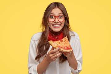 Photo of satisfied woman holds piece of pizza, feels pleased as spends free time with friends in pizzeria, looks happily directly at camera, wears casual outfit, isolated over yellow wall. Lunch