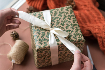 men's hands tie a white bow on a box with a Christmas gift,