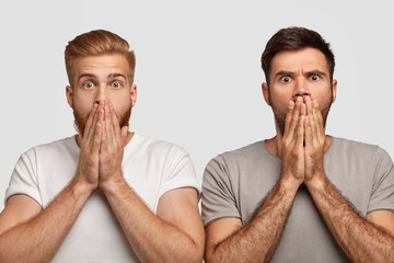 Stupefied emotive bearded guys cover mouthes with palms, dressed in casual clothes, feel astonished while watch horror film, isolated over white background. People and facial expressions concept