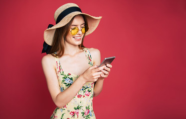 Smiling young blond lovely woman in dress and hat is standing with smart phone in hands and surfing in internet