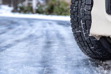 スタッドレスタイヤのクローズアップ / 北海道の雪道イメージ