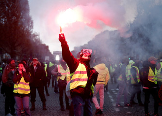 A protester wearing yellow vest, a symbol of a French drivers' protest against higher fuel prices, burns flare on the the Champs-Elysees in Paris