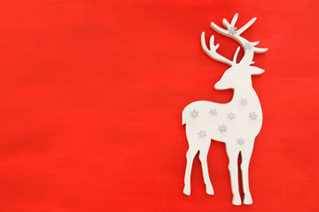 Top vie image of white wooden christmas deer over red background. Flat lay