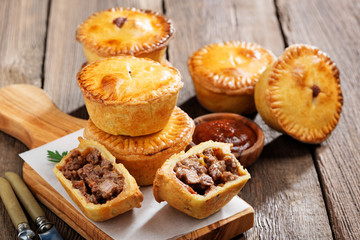 Traditional Australian Mini meat pies from shortbread dough on a wooden board over wooden background.