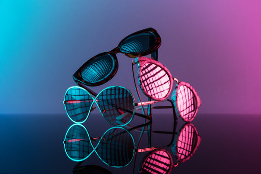 Sunglasses stacked in a pile with vivid color, hot pink and blue.