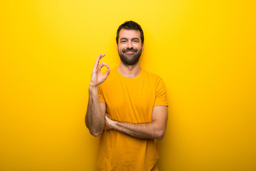 Man on isolated vibrant yellow color showing an ok sign with fingers Wall mural