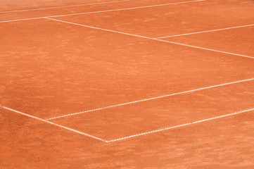 Part of empty used red clay tennis court playground surface with white lines closeup