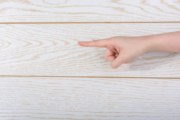 Hand making pointing gesture on wooden background