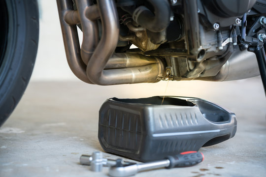 Maintenance engine concept : Drain the old oil from the engine through the drain plug. Changing the oil in a motorcycle engine, for Replacing and pouring fresh oil into motorbike engine at garage.