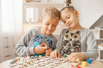 Preschoolers play and learn English letters using wooden alphabet.