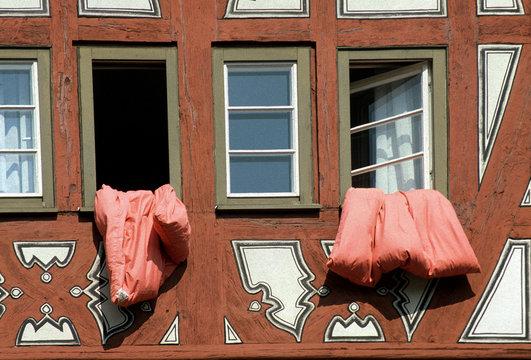 rote Bettwäsche hängt zum Lüften aus einem Fenster im Fachwerkhaus
