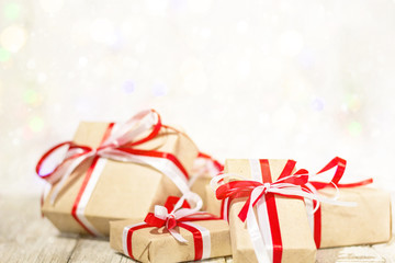 Christmas gift box against bokeh background. Holiday greeting card decorated with snow