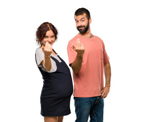 Couple with pregnant woman presenting and inviting to come with hand on isolated white background