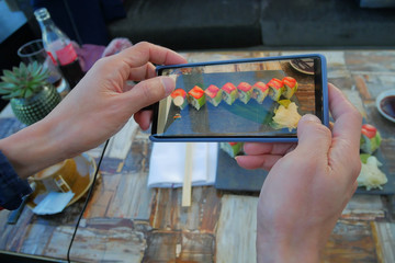 Happy time of young man using smart phone taking photo which take a picture sushi before eating of a plate with Japanese food