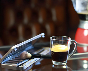 Cup of coffee with the phone and make-up set and brushes