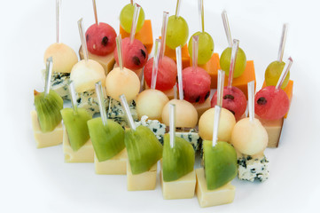 Catering for party. Close up of appetizers with watermelon, grapes, melon, kiwi, cheddar, parmesan, blue cheese over white plate