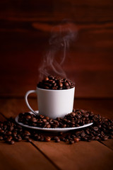 A white cup full of hot coffee beans on a wooden table