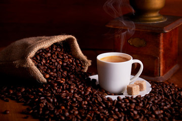 Cup of espresso with coffee beans and old ginger on wooden table