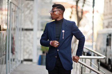 Amazingly looking african american man wear at blue blazer with brooch, black turtleneck and glasses posed at street. Fashionable black guy.