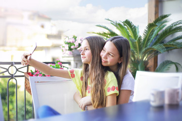 Two teen girls have fun and make selfie with the smartphone