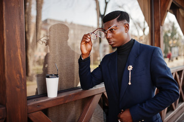 Amazingly looking african american man wear at blue blazer with brooch, black turtleneck and glasses posed at street. Fashionable black guy with cup of coffe.
