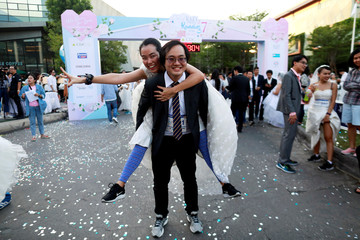 A bride and bridegroom pose for a photo after  'Running of the Brides' race event in Bangkok
