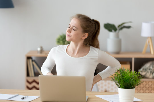 Exhausted girl stretch in chair having spasm working too long in incorrect posture, tired female sit at home desk suffer from back pain, massage trying to relieve symptoms. Sedentary lifestyle concept