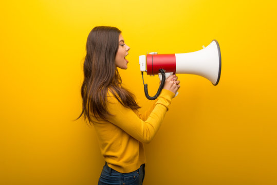 Teenager girl on vibrant yellow background shouting through a megaphone to announce something in lateral position