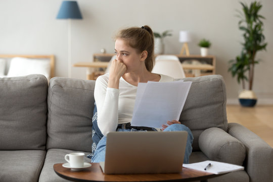 Unhappy young female sit on couch at home working at laptop reading paperwork, sad girl studying indoors looking away thinking of something, tired young woman distracted from computer job dreaming