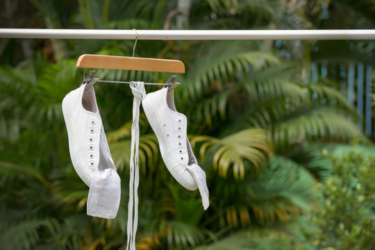 White sneakers hanging on clothesline with hanger in the sun.