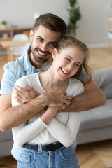 Portrait of happy husband hold in arms young wife posing at home, excited millennial couple hugging looking at camera making family picture in living room, loving man and woman embrace laughing