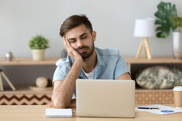 Exhausted millennial male hold head with hand sitting at office table falling asleep, tired man fall asleep working at laptop at home workplace, sleepy guy feel fatigue taking nap near computer Wall mural