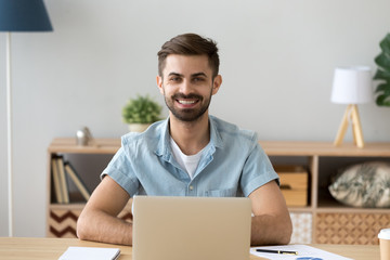 Portrait of happy millennial man sitting at office desk working with laptop and paperwork from home, headshot of smiling male student posing at workplace using computer studying looking at camera