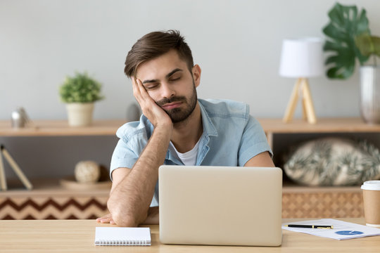 Exhausted millennial male hold head with hand sitting at office table falling asleep, tired man fall asleep working at laptop at home workplace, sleepy guy feel fatigue taking nap near computer