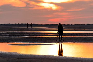 female photographer with tripod at beach against sunset