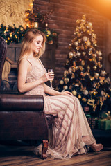 Elegant young blonde woman in a long Golden dress sitting on a chair and drinking champagne, holding a wine glass on the background of Christmas decorations