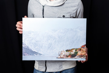 A man holds in his hands a landscape (mountains, sea, lighthouse) photography  printed on canvas