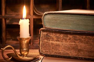 Alte Bücher auf Holztische bei Kerzenlicht