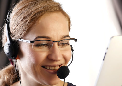 businesswoman talking on a headset in an office. customer service proffessional.