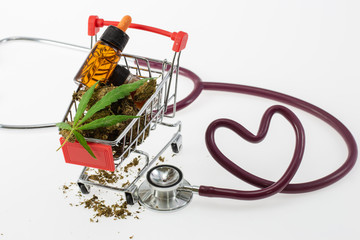 Stethoscope in Shape of Heart and Green Cannabis Leaf oil in shopping cart, healthy concept